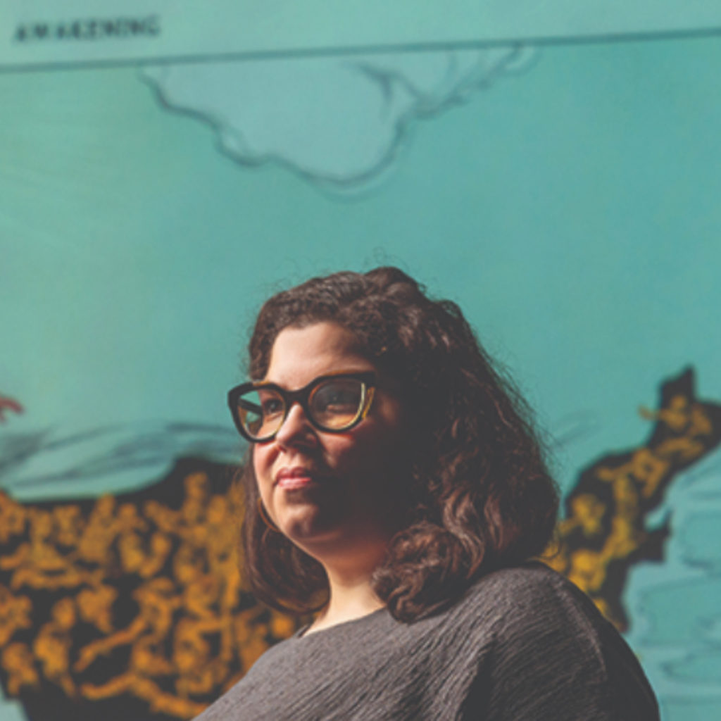 A woman with glasses and shoulder length hair poses in front of an image of a map