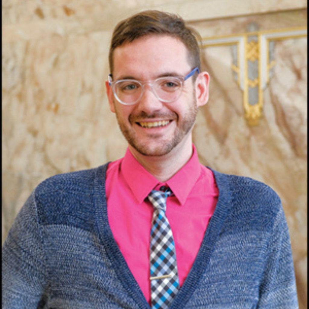 A man in a pink collared shirt and blue cardigan smiles for a portrait