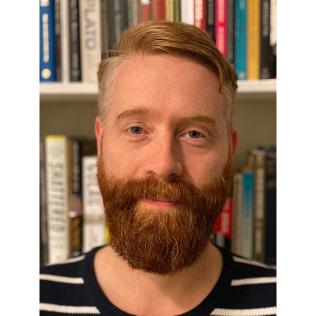 A man with a beard poses for a photo in front of a bookshelf
