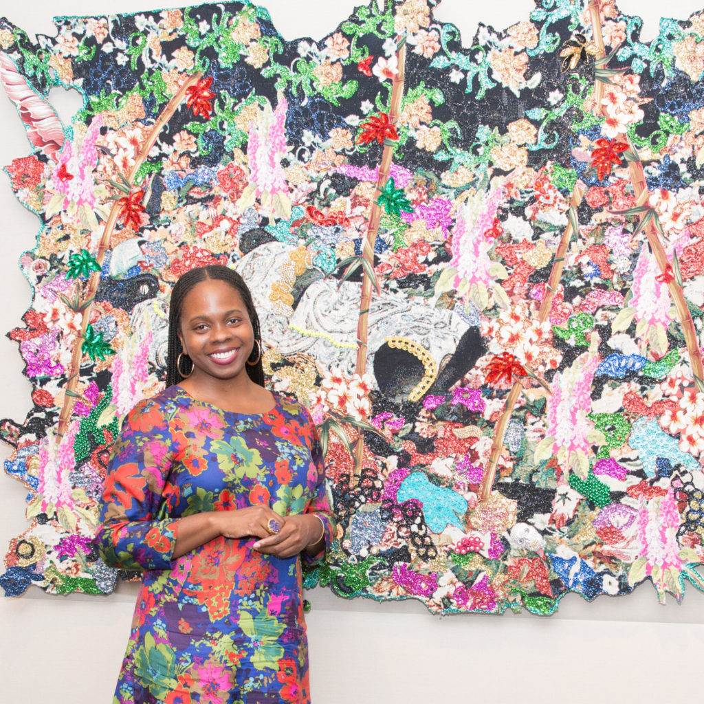 A woman smiles for a photo while posing in front of a large, colorful pink and green work of art on a wall