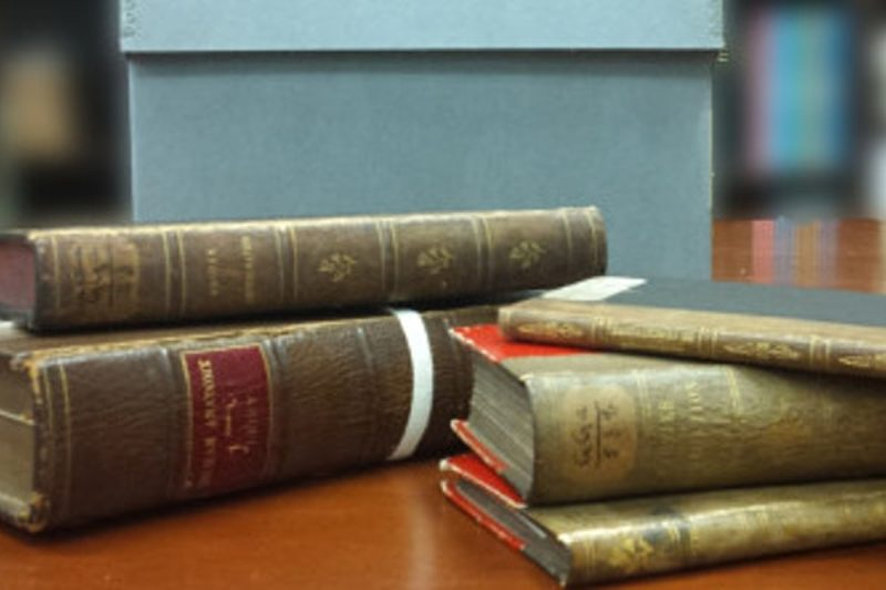 A set of old books of varying sizes on a table in the foreground. Archival boxes in the background.
